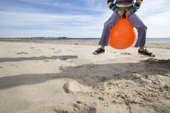 Girl (8-10) playing on inflatable hopper on beach, low section Stock Photo