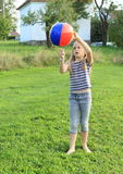 Girl playing inflating ball Royalty Free Stock Image