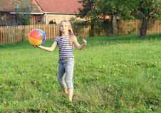 Girl playing with inflating ball Royalty Free Stock Photo