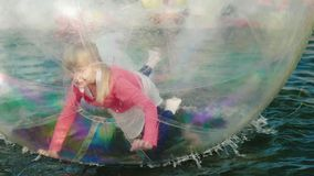 A girl is playing inside a transparent bowl that floats on the water. Entertainment in the amusement park stock footage
