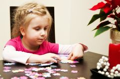 Girl playing with jigsaw puzzle. A cute young girl (four year old) playing with jigsaw puzzle while sitting at table at home royalty free stock image