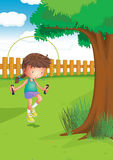 A girl playing with a jumping rope at the garden. Illustration of a girl playing with a jumping rope at the garden Stock Photography