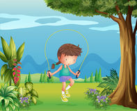 A girl playing jumping rope near the tree Stock Photo