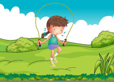 A girl playing jumping rope at the top of the hill Royalty Free Stock Photo