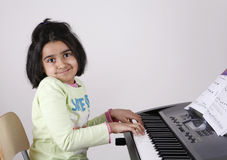 Girl playing keyboard Stock Images