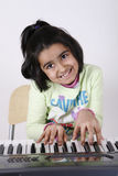 Girl playing keyboard Stock Image
