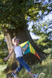 Girl (7-9) playing with kite in woodland clearing, smiling, side view (tilt, blurred motion) Royalty Free Stock Photography