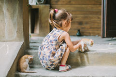 Girl playing with kittens on the terrace Stock Images