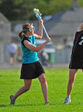 Girl playing lacrosse. Side view of high school girl in protective face mask playing lacrosse Stock Images