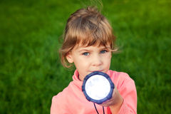 Girl playing with lantern on grass Royalty Free Stock Photos