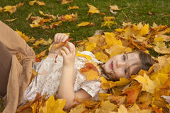 Girl Playing in Leaves. Young girl lying in the leaves playing Royalty Free Stock Photo