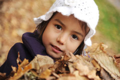 A girl playing with the leaves Royalty Free Stock Photos