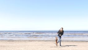 Girl playing with little doggy. At seaside stock video footage