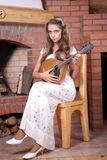 Girl playing on Mandolin. Girl in white dress playing on Mandolin near fireplace Royalty Free Stock Photos