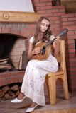 Girl playing on Mandolin. Girl in white dress playing on Mandolin near fireplace Stock Images