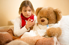 Girl playing and measuring teddy's bear temperature with thermom Stock Photos