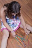 Girl playing mikado on the floor Stock Image