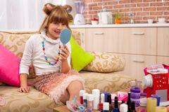 Girl playing with mom`s makeup Royalty Free Stock Images
