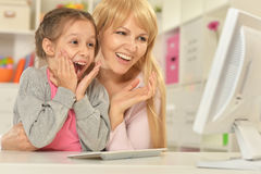 Girl playing with mother on computer Royalty Free Stock Image