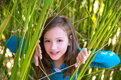 Girl playing in nature peeping from green canes. Beautiful little girl playing in nature peeping from green canes stock photography