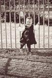 Girl playing near fence Stock Photos
