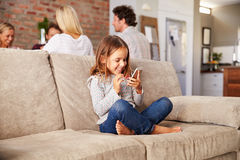 Girl playing with new technology while adults entertain Stock Images