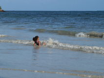 Girl playing in ocean waves Stock Photos