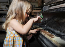 Girl playing on an old piano. Stock Photography