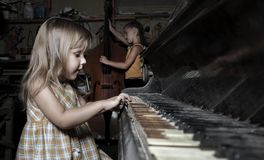 Girl playing on an old  piano Stock Photos