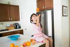 Girl playing with an orange in the kitchen stock images