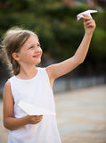 Girl playing outdoors. Happy girl playing with simple paper airplane toy on sunny day in town Stock Photos