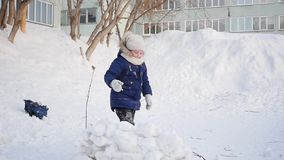 Girl playing outdoors in winter. Children throw snowballs stock video