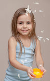Girl playing with paper. Little girl throwing crumpled pieces of paper in the air royalty free stock photography