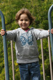 Girl playing in park. Cute young girl playing on apparatus in park with green leafy background Stock Photography