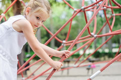 Girl playing in the park.  Little girl climbing on outdoor playg Royalty Free Stock Images
