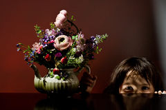 Girl playing peek-a-boo with flowers Royalty Free Stock Photos