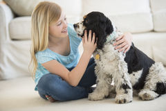 Girl Playing With Pet Dog In Living Room. Little girl playing with pet dog in living room Royalty Free Stock Photo