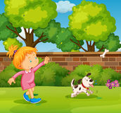 Girl playing with pet dog in the yard Stock Photo