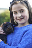 Girl Playing With Pet Guinea Pig Outdoors In Garden royalty free stock image
