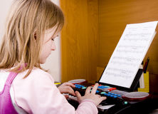 Girl playing at piano Royalty Free Stock Photography