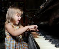 Girl playing on an  piano. Stock Photos