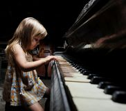 Girl playing on an  piano. Girl playing on an old black piano Stock Images