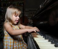 Girl playing on an  piano. Stock Image