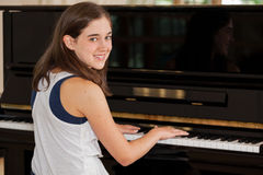 Girl Playing Piano. An 11 year old girl looking over her shoulder at the piano Stock Photos