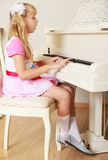 Girl playing the piano. Beautiful little blonde girl plays the piano and sings Stock Photos