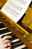 Girl playing the piano Stock Images