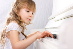 Girl playing on piano Stock Photos
