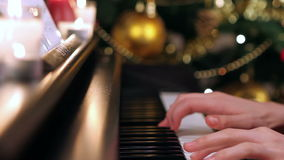 Girl playing piano near Christmas tree