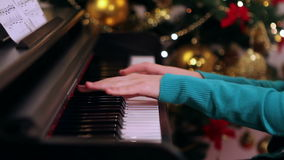 Girl playing piano near Christmas tree stock video footage