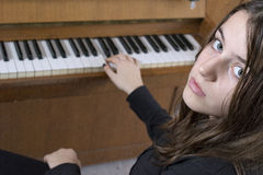 Girl playing the piano with one hand Stock Photography